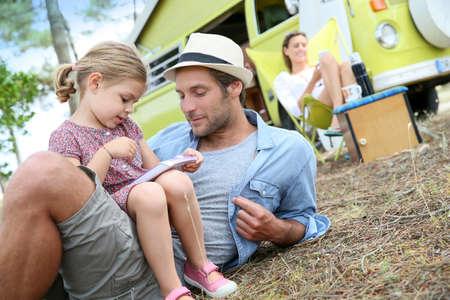 niños sentados: Papá con niña jugando juntos en camping