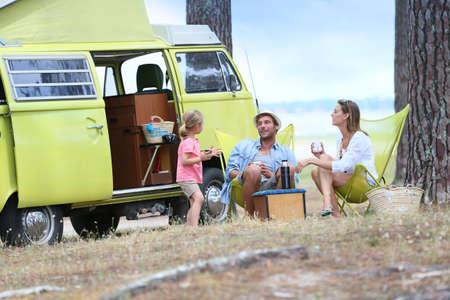 vans: happy family relaxing by camper van in summer Stock Photo