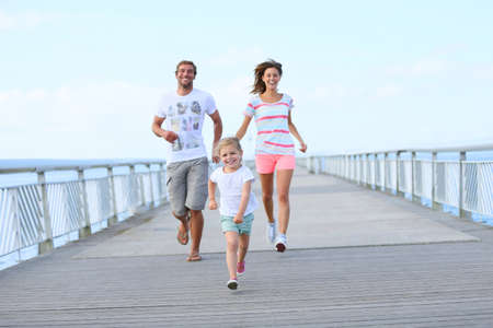 3 4 length: Little girl with parents running on a bridge