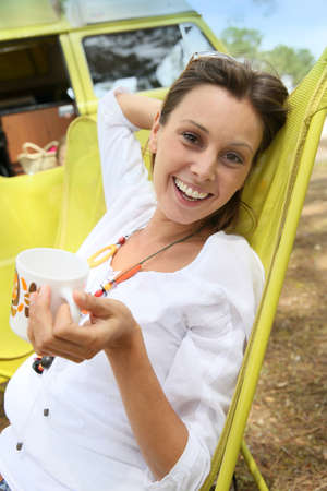 campground: Portrait of cheerful woman relaxing in chair on campground