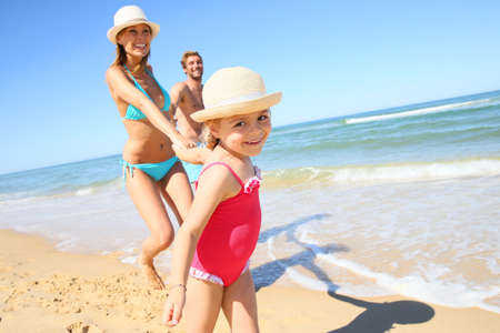 the child laughing: Portrait of little girl running on beach with parents Stock Photo