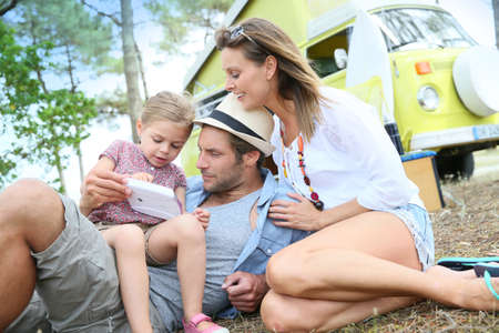 Family playing with video game on campground