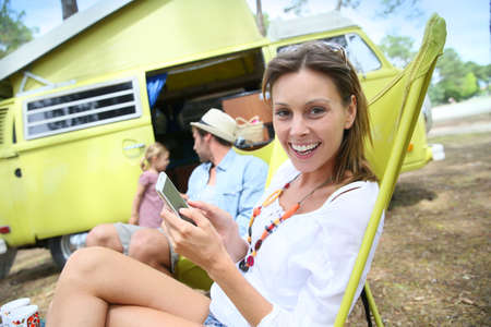 camper: Portrait of cheerful woman relaxing in chair on campground