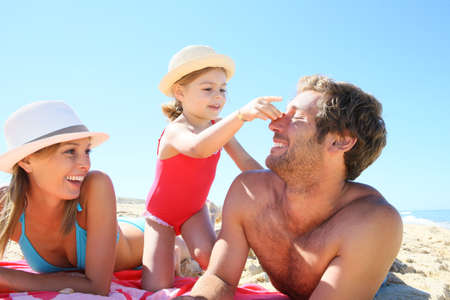enfant qui joue: Famille jouant avec des coquillages sur la plage Banque d'images