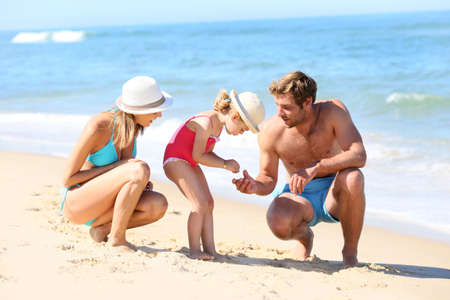 the child laughing: Parents with little girl playing on a sandy beach