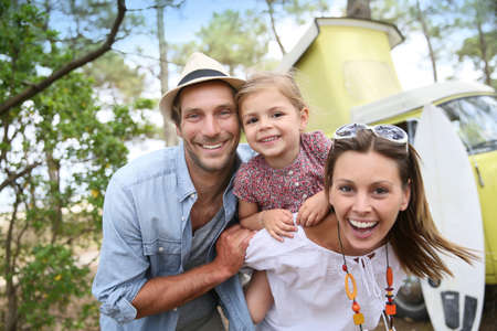 Couple with little girl enjoying vacation in camper van Stockfoto