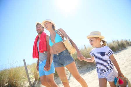 dia soleado: Familia caminando a la playa en un día soleado