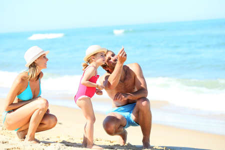 bikini couple: Parents with little girl playing on a sandy beach