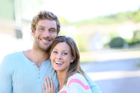 the property: Portrait of cheerful couple standing in new property walkway