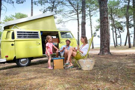 camper: happy family relaxing by camper van in summer Stock Photo