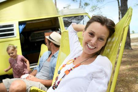 relajado: Retrato de mujer alegre que se relaja en silla en camping