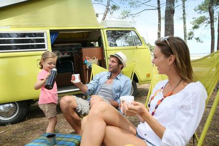 gelukkig gezin ontspannen bij camper in de zomer