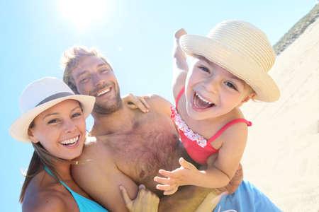 Fröhlich Eltern halten kleines Mädchen mit Waffen am Strand