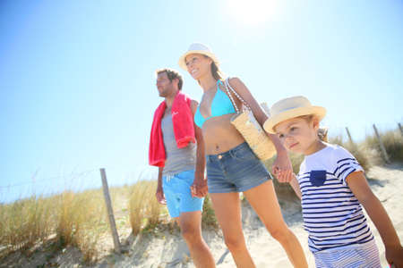 Family walking to the beach on a sunny day photo