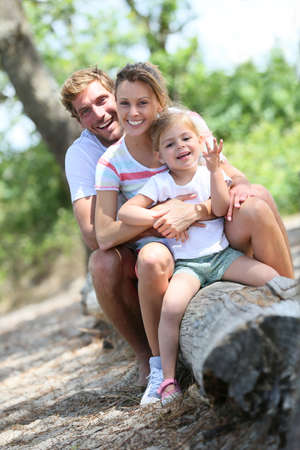 family portrait: portrait of happy family sitting on a trunk