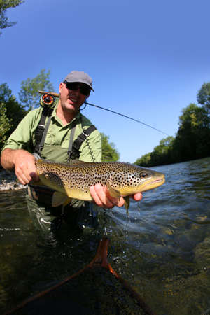 fishing gear: Closeup of fly-fisherman holding brown truit in river