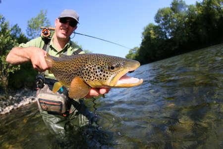 Primer de la mosca pescador sostiene Truit marrón en el río