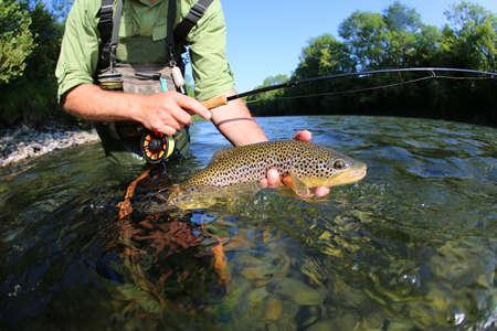 Nahaufnahme von Fliegenfischer hält braun truit in Fluss Lizenzfreie Bilder