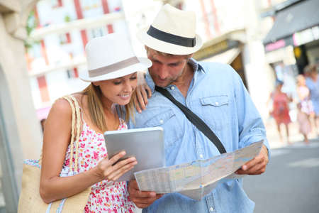 honeymoon: Couple in vacation looking at tourist guide on internet