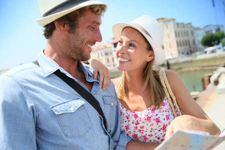 basque woman: Couple of tourists at seaside resort looking at city map