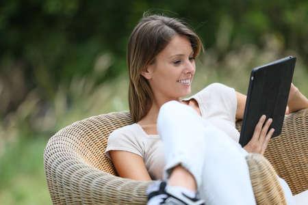 relajado: Mujer que se relaja en el sill�n al aire libre y el uso de la tableta digital Foto de archivo