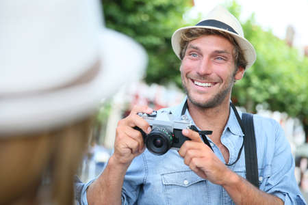 ttractive: Trendy guy with hat taking picture of woman with vintage camera