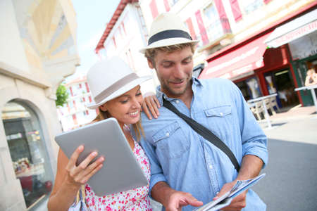 guide: Couple in vacation looking at tourist guide on internet