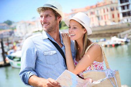 luna de miel: Pareja de turistas en la zona costera mirando el mapa de la ciudad Foto de archivo