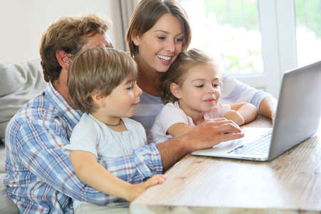 usando computadora: Los padres con niños en casa utilizando el ordenador portátil