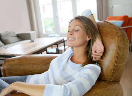 Young woman at home relaxing in armchair