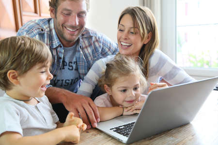 Parents with kids at home using laptop computer Stock fotó