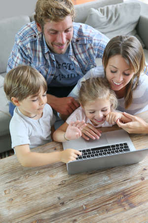 kids laptop: Parents with kids at home using laptop computer Stock Photo