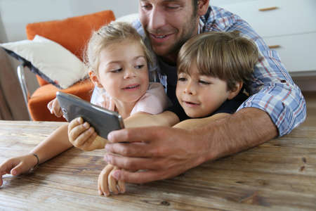 Daddy with kids playing with smartphone