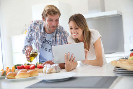 hombre cocinando: Pares alegres en cocinar la cena de la cocina, que usa la tableta