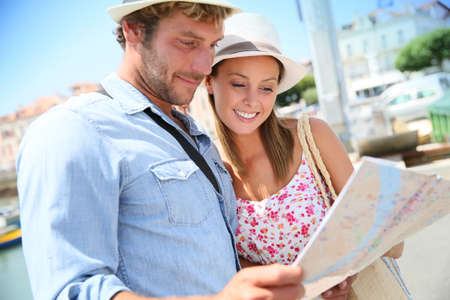 seaside resort: Couple of tourists at seaside resort looking at city map