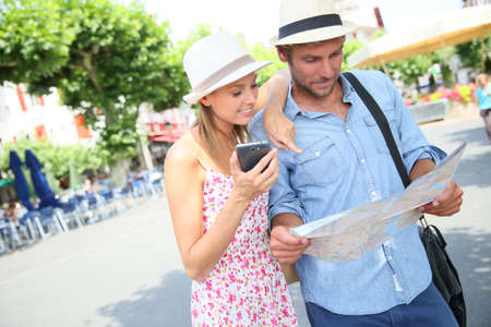 basque woman: Couple of tourists looking at map in city square Stock Photo