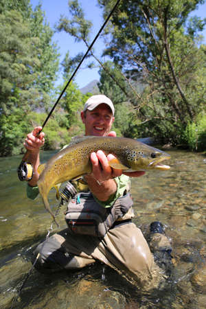 fishing equipment: Fly fisherman holding brown trout in stream water