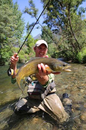 hombre pescando: Pescador de la mosca de la trucha marr�n que sostiene en agua corriente