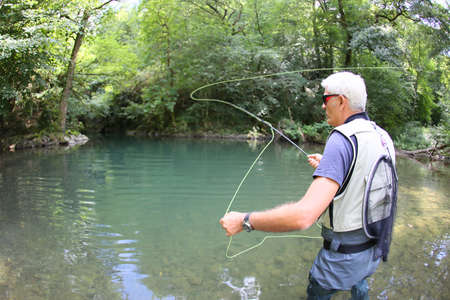 wader: Fly-fisherman fishing in river on summer season
