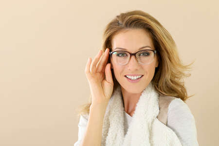 winter fashion: Attrative trendy mature woman with eyeglasses, isolated Stock Photo