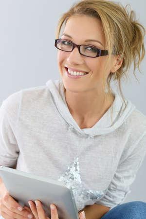 anteojos: Mujer sonriente que usa la tableta digital, aislado