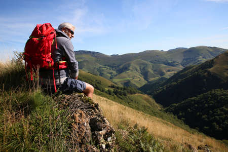 admiring: Hiker sitting on a rock admiring Basque Country scenery Stock Photo