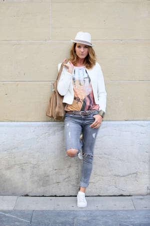 modelos posando: Mujer de moda apoyándose en la pared de la ciudad Foto de archivo