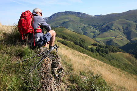 the basque country: Hiker sitting on a rock admiring Basque Country scenery Stock Photo