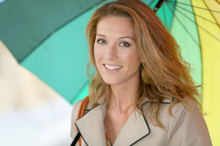 blonde woman: Woman on a rainy day walking with umbrella