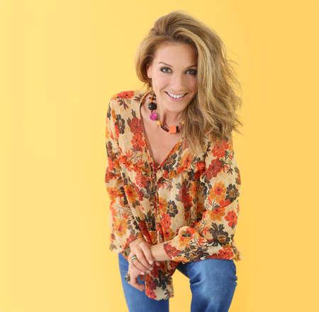 Mooie trendy vrouw, geïsoleerd op een gele achtergrond