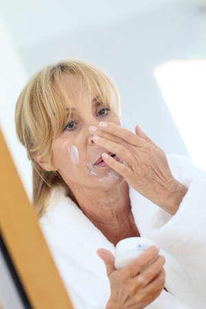 facial cream: Elderly woman applying facial cream on her skin Stock Photo