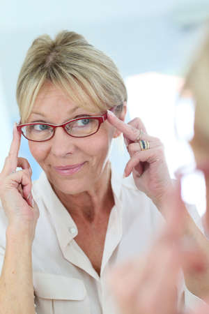 trying: Elderly woman trying eyeglasses on in front of mirror