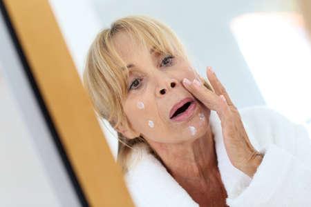 woman face cream: Elderly woman applying facial cream on her skin Stock Photo
