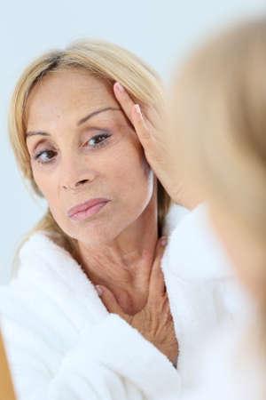 aging: Elderly woman applying facial cream on her skin Stock Photo